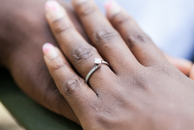 Hands of an nigerian couple. She is wearing an engagement ring.