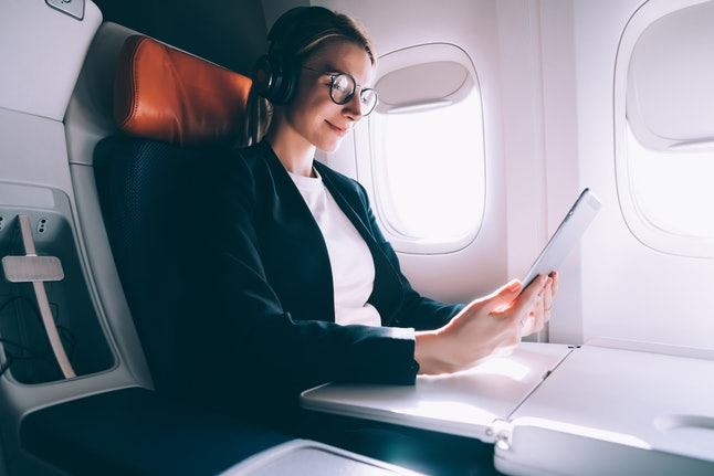 Charming female in bluetooth earphones for noise cancellation watching online webinar during comfort flight in airplane, woman browsing network on digital tablet while connecting to wireless hotspot