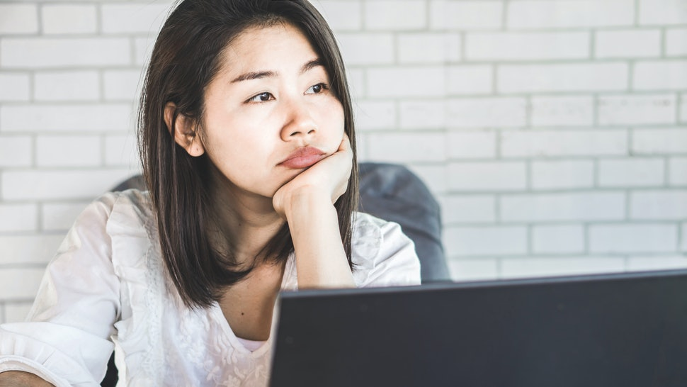 unmotivated Asian female worker sitting at desk bored to work thinking of  quitting job