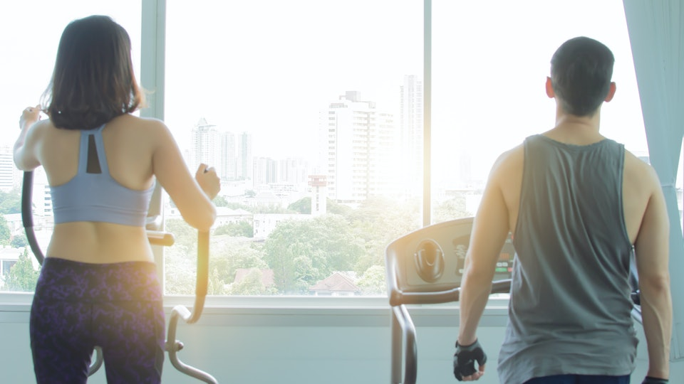 Back of a couple is exercising in fitness center in the morning with the warm light and cityview outside the window