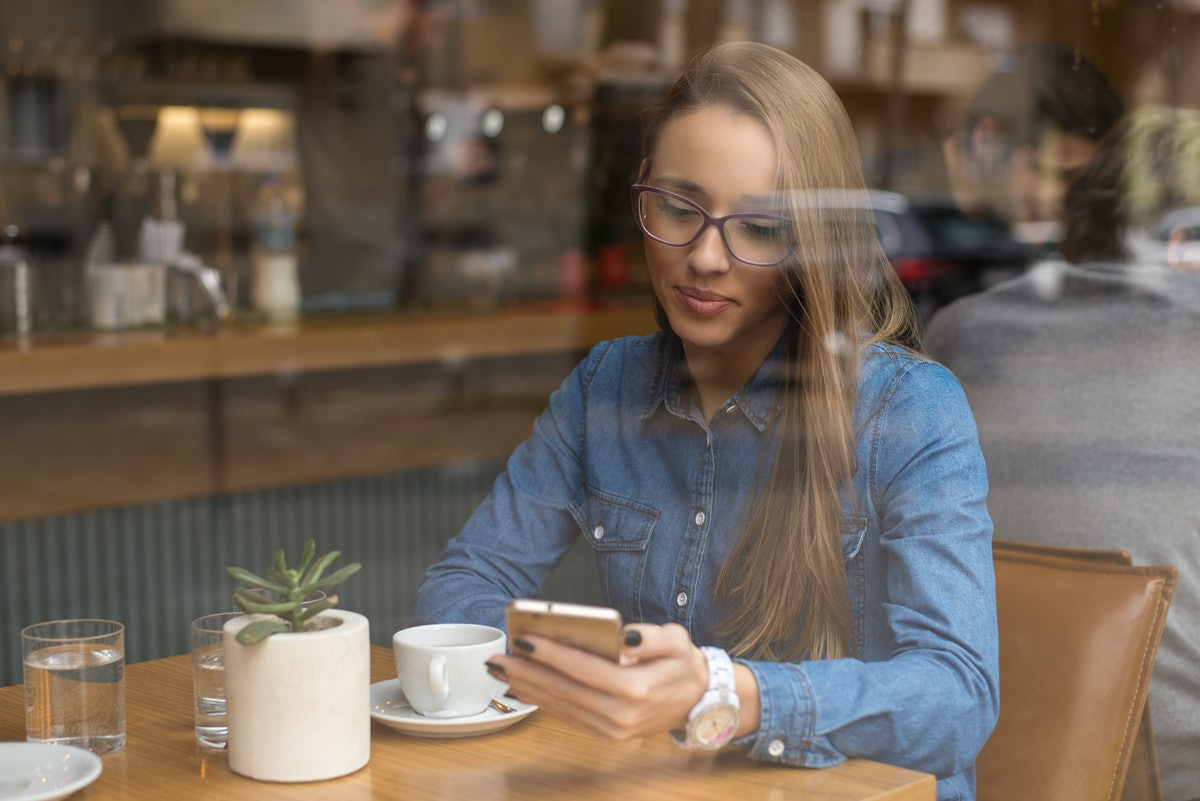 Pretty woman drinking coffee and texting a message