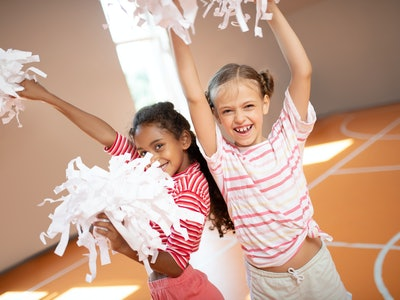 Girls laughing. Beautiful little girls wearing sport clothing laughing while practicing cheerleading