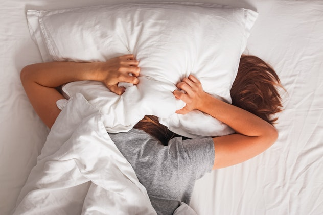 Woman lying in bed and covering her head with pillow. Struggling from insomnia, noise or early morning get up.
