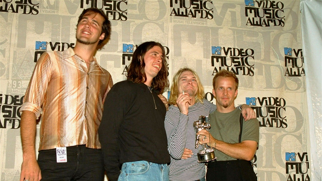 """Nirvana Nirvana band members, Chris Novoselic, from left, Dave Grohl, and Kurt Cobain pose, with an unidentified man, right, after receiving an award for best alternative video for """"In Bloom"""" at the 10th annual MTV Video Music Awards in Universal City, Calif. Cobain's widow and daughter are urging a Seattle judge not to release death-scene photos and records that a lawsuit claims will prove the Nirvana frontman was murdered more than 20 years ago. Superior Court Judge Theresa Doyle is set to hear arguments, over whether to proceed with a trial after Richard Lee, who runs a Seattle public access TV show, sued the city and the Seattle Police Department for the material he says will show Cobain didn't die of a self-inflicted gunshot wound in 1994, The Seattle Times reported"""
