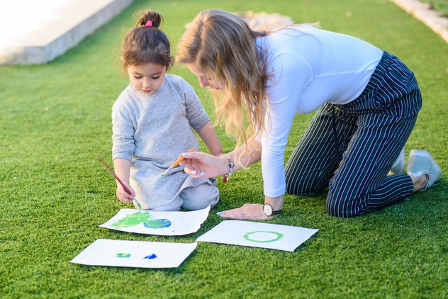 Happy loving family. Mother and daughter drawing and having fun. Child and babysitter painting with brush and color a picture of earth sitting on the grass in the summer park.