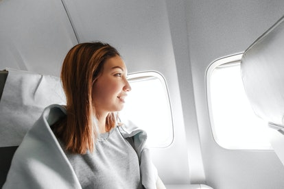 Young asian woman looking at the window in air plane, travel and transport concept