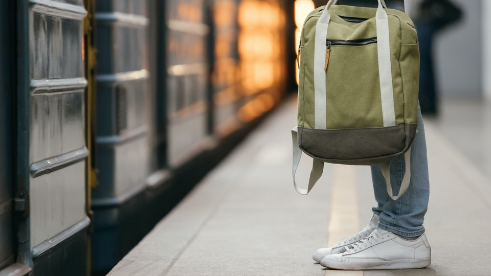 Close up photo of male waiting subway train on platform. Well-dressed handsome man in white sneakers and jeans with backpack in hand standing on station. Modern citizen of big city. Lifestyle concept.