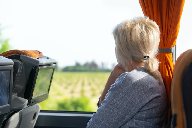 Woman looking out of the window of a coach or train watching the passing countryside as she travels ...