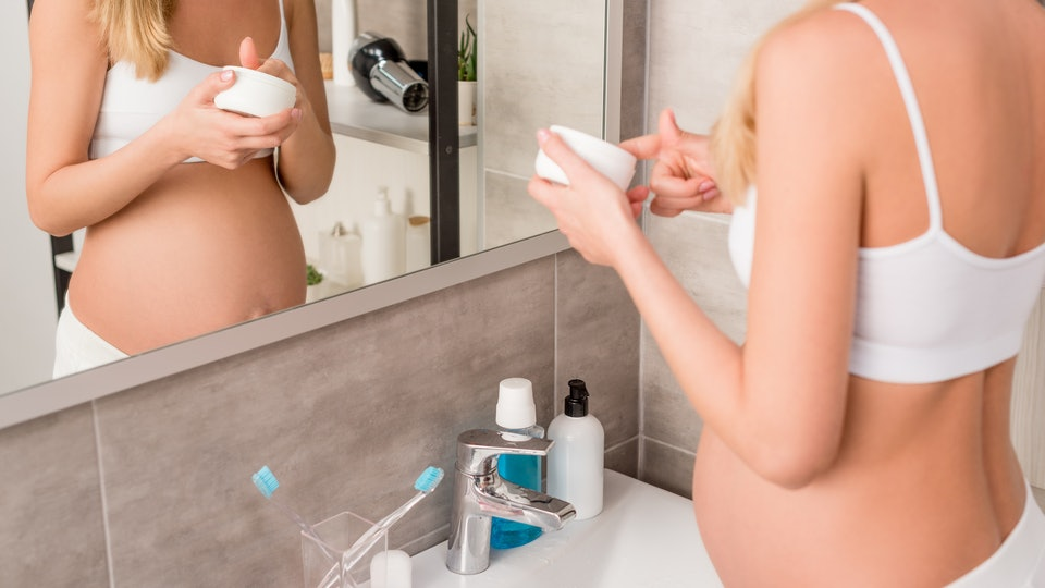 cropped shot of pregnant woman with jar of cream standing in front of mirror in bathroom