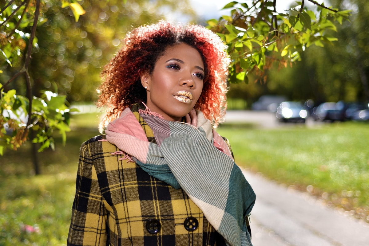 portrait of pretty dark-skinned beautiful girl with red curly magnificent hair. woman in plaid coat ...
