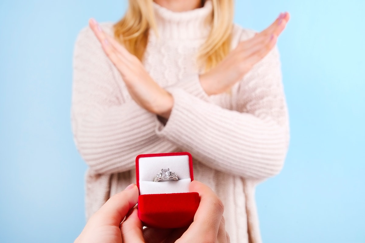 She said NO concept. Young girl rejects the marriage proposal. Woman refuses the engagement gold platinum diamond ring, man male & female hands crossed close up, NO gesture. Background, copy space.