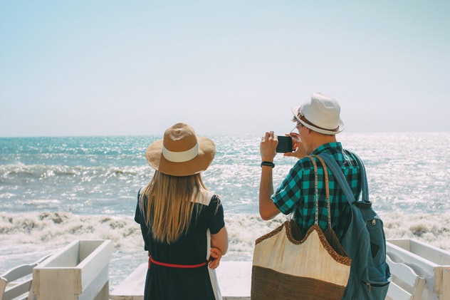 Couple woman and man looking and making photo at the stormy sea