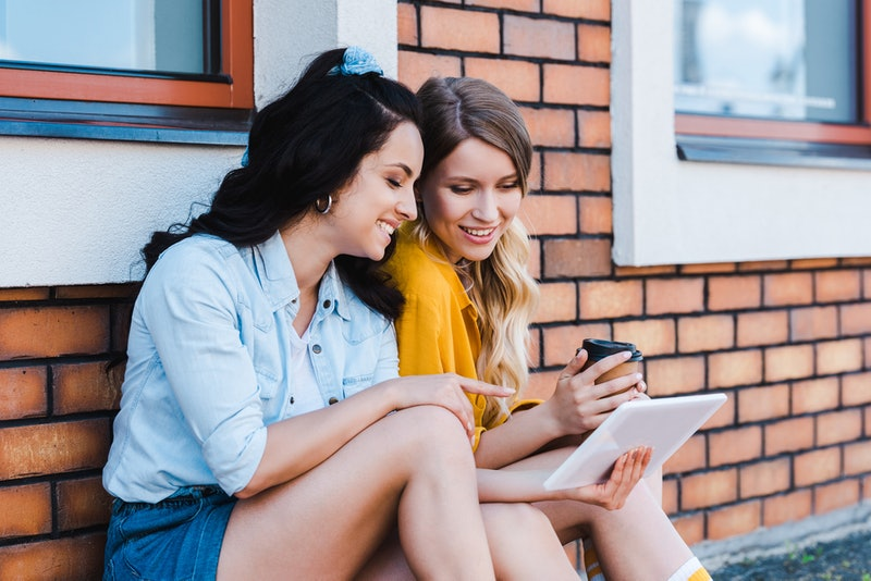 happy woman pointing with finger at digital tablet near girl
