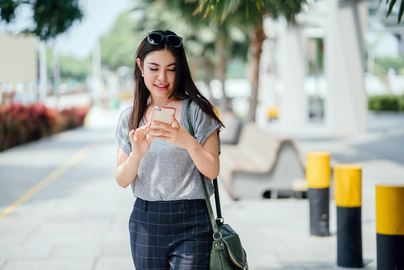Portrait of a young and beautiful Japanese Asian woman standing on a bridge during the day. She is a tourist and is posing for her portrait photograph of herself to post on Instagram.