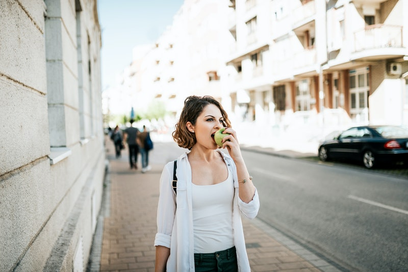 Attractive young woman walking on street and eating an apple.