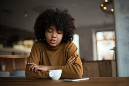 A woman in a sad mood is sitting alone and bored, she is waiting for her boyfriend to call in a coffee shop and drink coffee. Relationships, parting, melancholy, mood