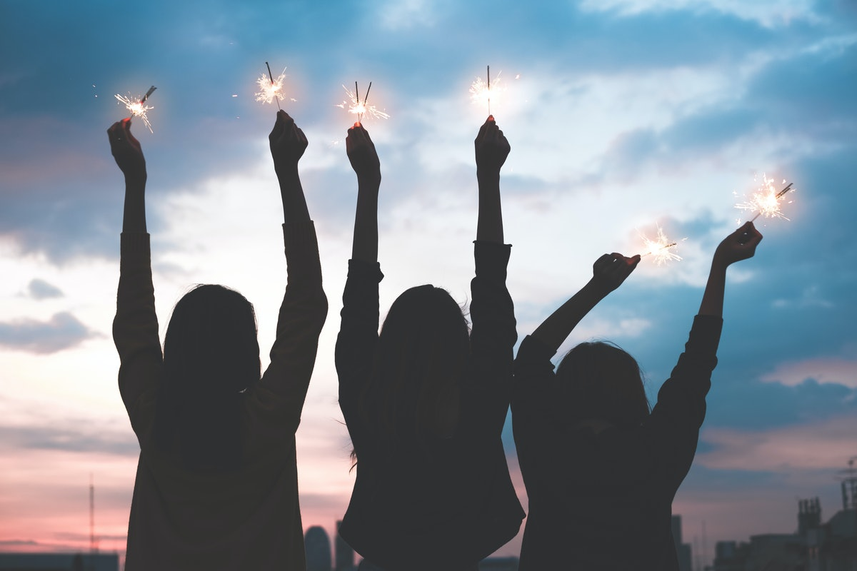 silhouette happy group of asian young girl friends hangout enjoy and play sparklers firework at night rooftop new year party at evening sunset,Holiday celebration festive,teenage people lifestyle