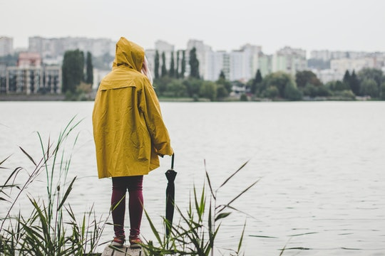 autumn gray rainy day concept of young teenager person in yellow raincoat stay back to camera on small wooden pier near river shire on foggy city buildings background