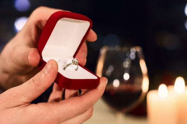Man's hands holding box with ring making proposal. Proposal on Valentine day concept