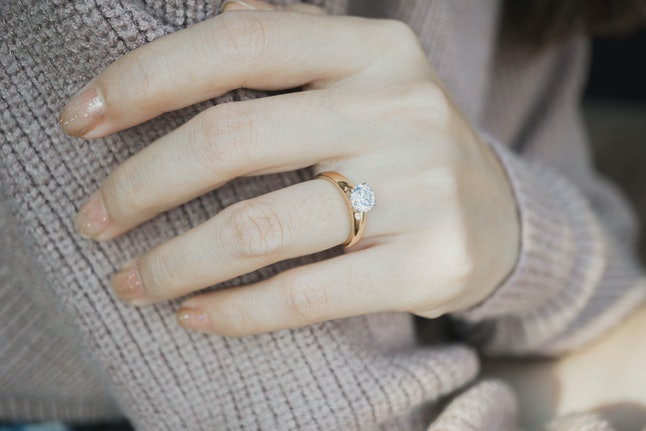 Close up of an elegant engagement diamond ring on woman finger with dark pink sweater winter clothe. love and wedding concept.soft and selective focus.