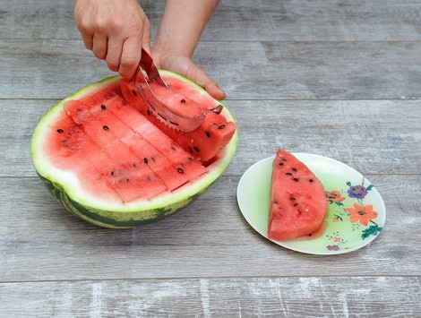 Preparing vegan food made of watermelon sliced with a slicer