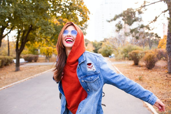 Autumn woman in autumn park. Warm sunny weather. Fall concept.cheerful fashion girl going crazy making funny face and dancing outdoor, hipster style