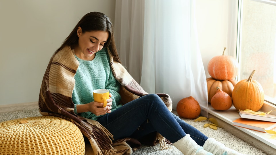 Woman drinking tea while resting at home on autumn day