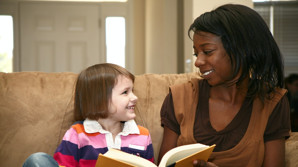 Beautiful african american woman reading to a 5 year old girl at home.