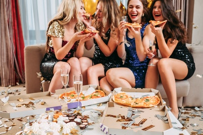 Girls hangout. Young ladies celebrating birthday party at home, eating pizza, drinking champagne, having fun. Confetti around.
