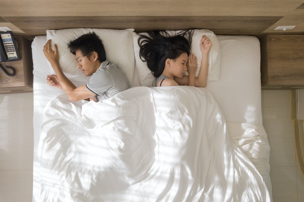 Top view of sad Asian couple sleeping together, thinking about relationship problems, and suffering from depression on bed with white blanket,