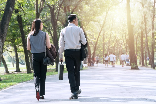 The back of couple businessman and businesswoman walking together within the park relaxed after work. Two businessmen holding cup of coffee walk talk happily in the park. Relaxing concept