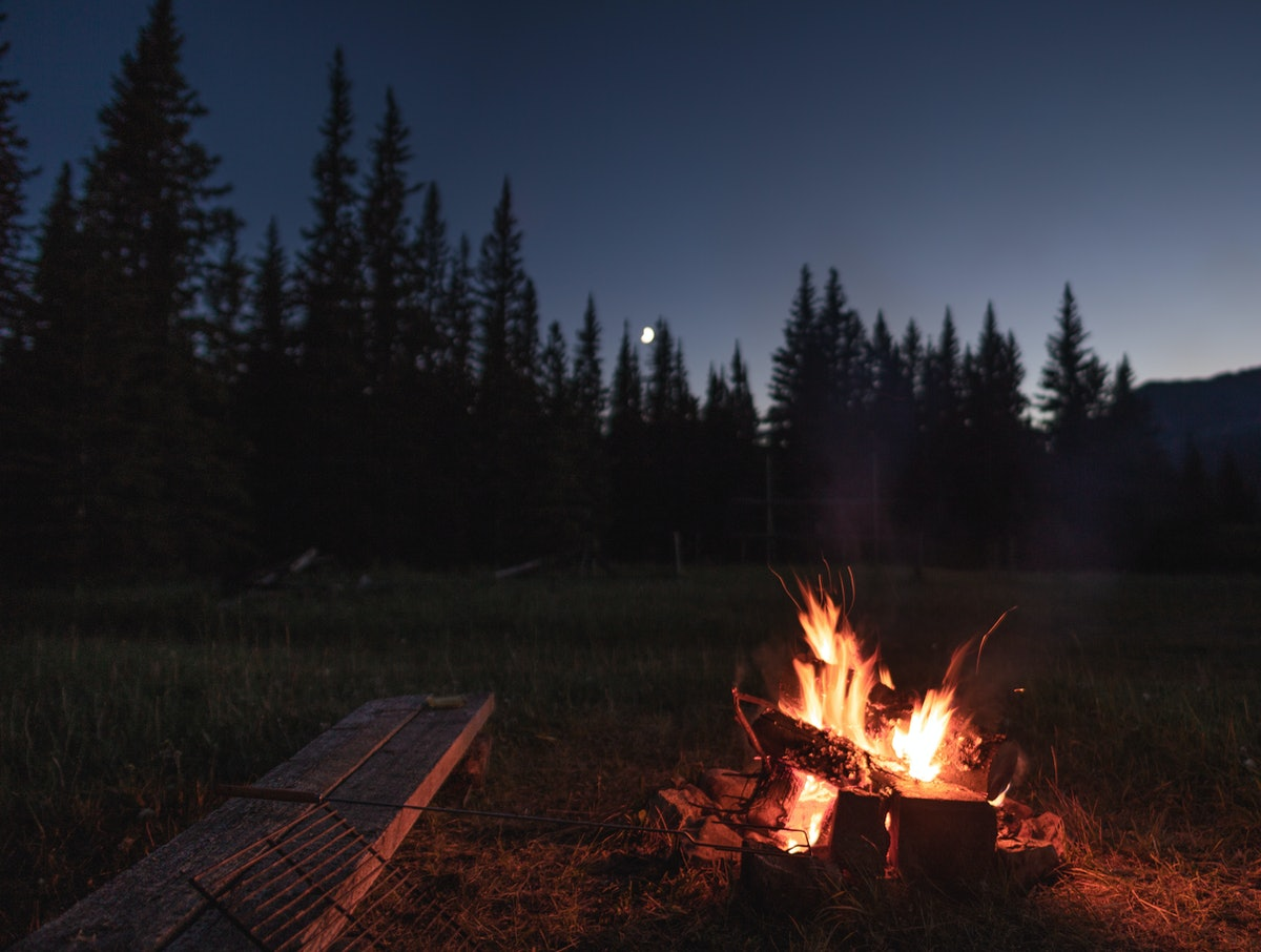 Campfire under the out of focus moon. There is a wooden bench beside the campfire with a hot dog / m...