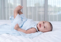 little baby move leg in the air on a bed