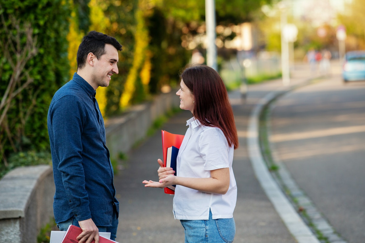 Young students smiling and speaking to each other in the city while taking a walk. Young students ou...