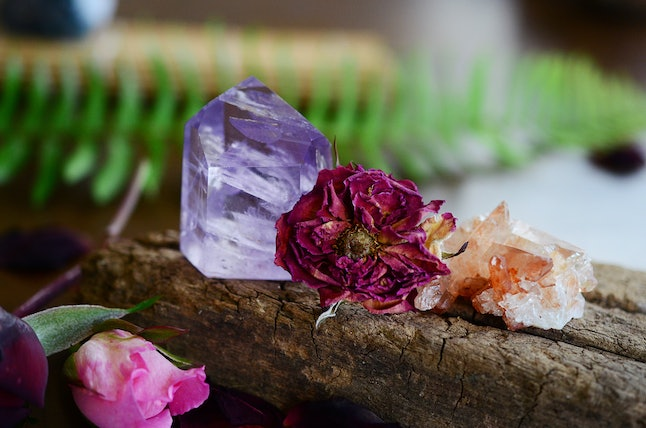 Beautiful Amethyst tower, lots of rainbows. Beautiful polished amethyst tower. Bright Quartz crystal, healing crystal being held in hand. Woman holding amethyst tower, natural lighting, reiki energy
