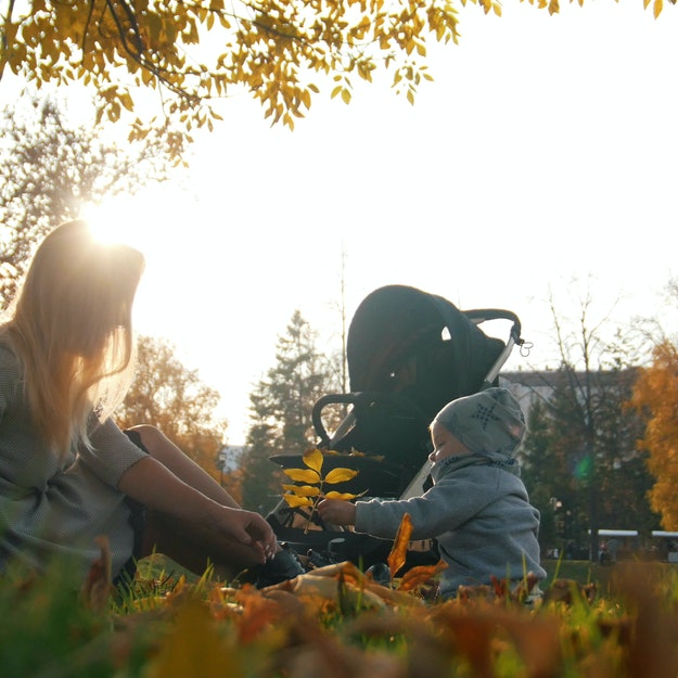 Young mother playing with leaves with her laughing little baby in autumn park