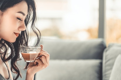 Asian young woman drinks coffee in the morning while sitting on sofa couch.
