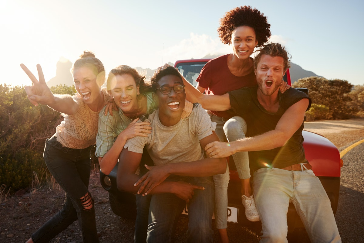 Five millennial friends on a road trip have fun posing for photos at the roadside, lens flare