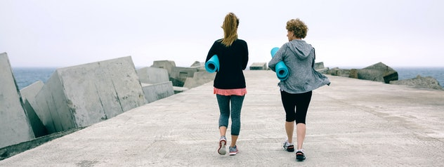 Back view of two unrecognizable women walking outdoors by sea pier