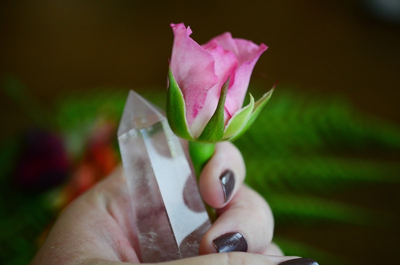 Beautiful Clear Quartz tower, and fresh pink rose flowers. Bright Quartz crystal, healing crystal being held in hand. Woman holding quartz tower, crisp colors in natural lighting. Vibrant meditation.