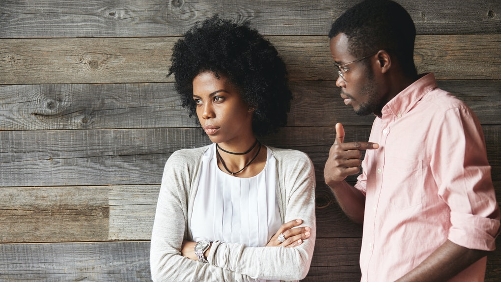 Dark-skinned man standing next to his offended wife with Afro haircut and crossed arms, man looking guilty, pointing finger at him, asking what he did wrong, trying to understand what happened to her