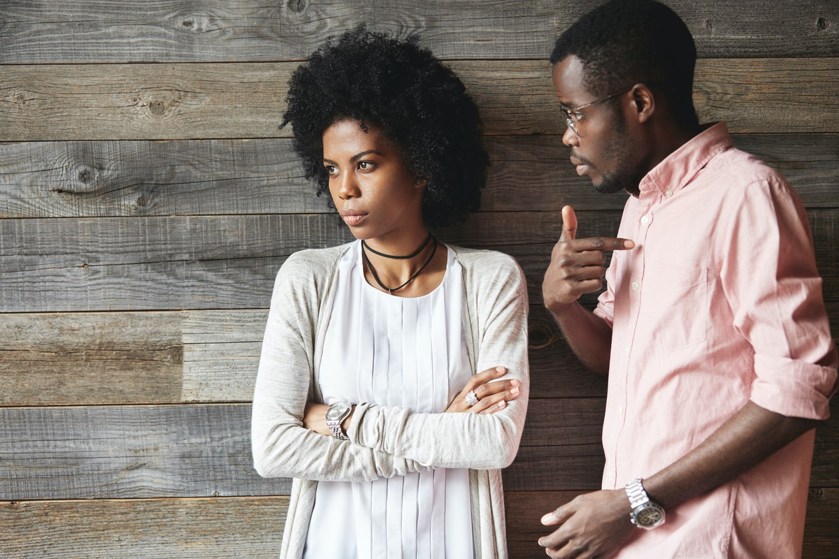 Dark-skinned man standing next to his offended wife with Afro haircut and crossed arms, man looking ...