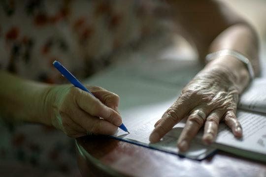 blue ballpoint pen in the hands of the old woman Is writing a book on a wooden table There is a light from the window coming back.