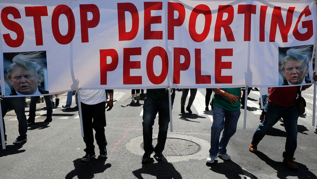 Protesters cast shadows as they walk with a sign during a May Day rally, in Los Angeles. Thousands of people took to the streets across the nation Monday to march in May Day rallies, calling for immigration reform, workers' rights and police accountability