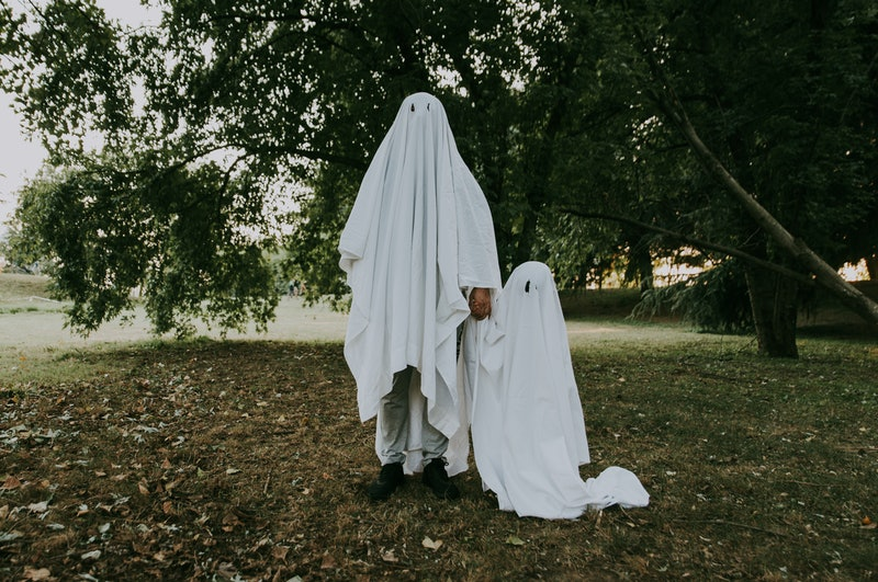 Father and son playing ghosts with white sheets in the garden, conceptual photos about halloween holidays