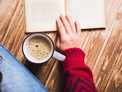 young woman in a red sweater holding a cup of coffee and reading a book