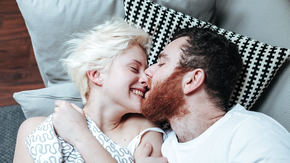 Closeup portrait of happy young couple in bed.
