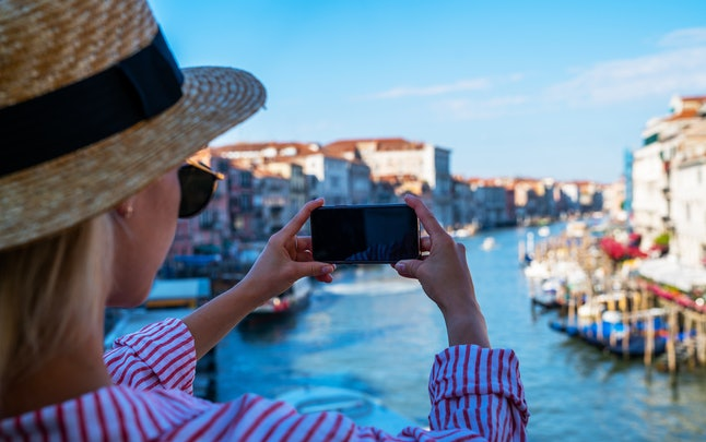 Panoramic view from the famous Rialto Bridge of Grande Canal in Venice, Italy. Outdoor summer lifestyle. Young woman with smartphone take travel photo.