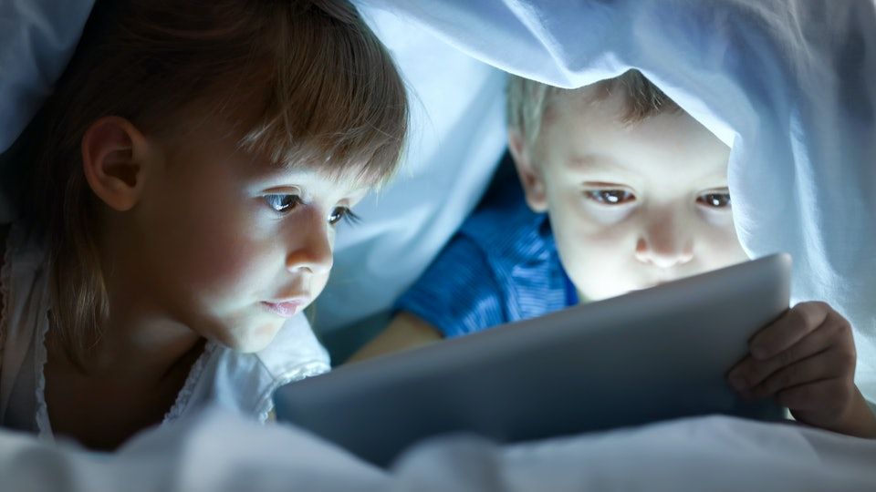 Cute little children lying under blanket with tablet computer