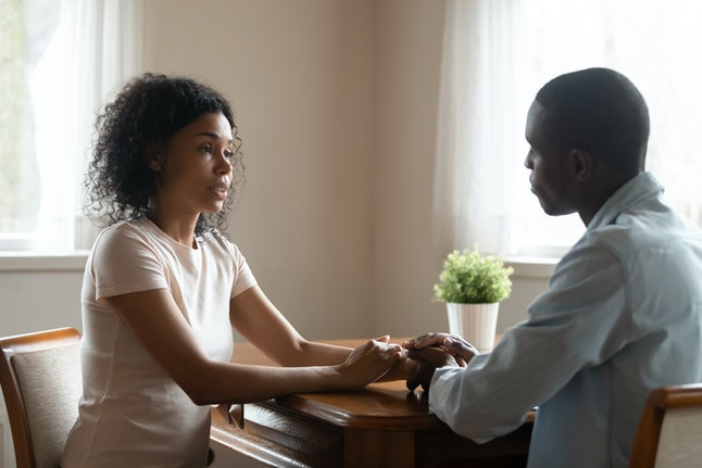 Serious african 30s married couple in love sitting at table having heart-to-heart intimate straight talk, mixed race wife holding hands of beloved black husband family share problems thoughts at home
